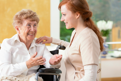 elderly woman talking to a friendly caregiver