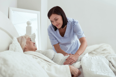 caregiver smiling while senior resting in bed