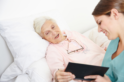 nurse reading book to senior